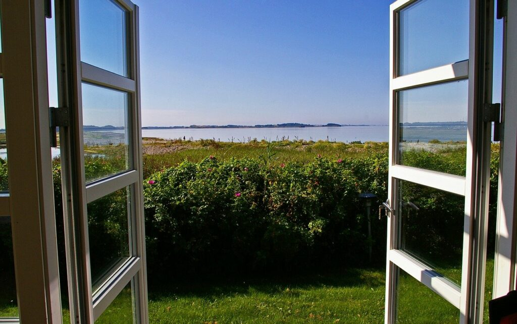 open window looking onto countryside with hinges visible